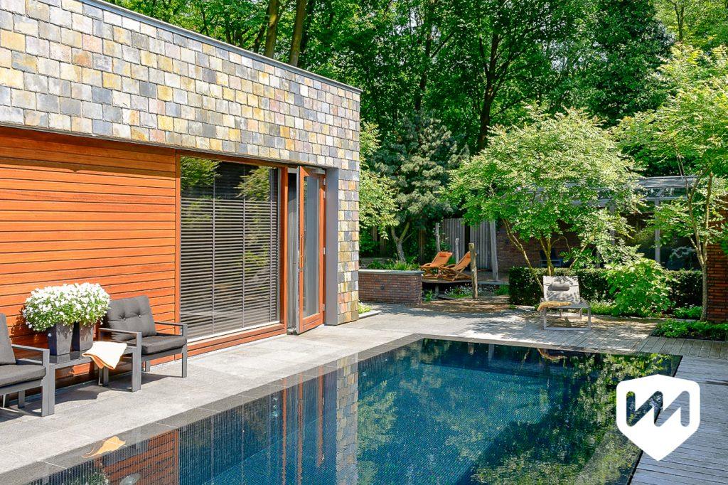 Moderne bostuin met luxe infinity overloop zwembad. Tuinarchitect door Van Mierlo Tuinen.