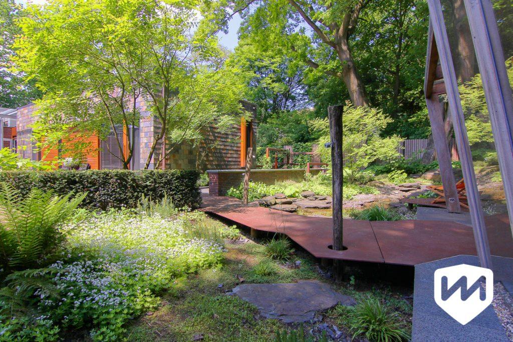 luxe natuurtuin met pad van roestige platen afgestemd op de architectuur van het huis. Tuinarchitect door Van Mierlo Tuinen.