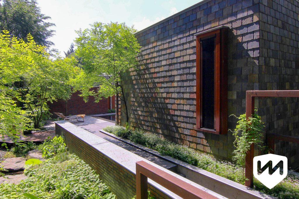 De materiaalkeuze van de trappartij met pergola is afgestemd op de fraaie vormgeving en de kleuren van het huis. Tuinarchitect Van Mierlo Tuinen.