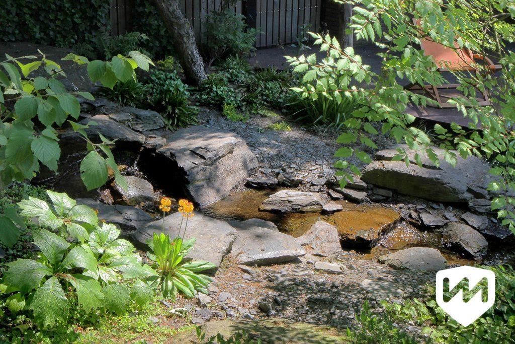 natuurlijke waterloop van zwerfstenen. Belgische ardennen. Bostuin. Tuinarchitect Van Mierlo Tuinen