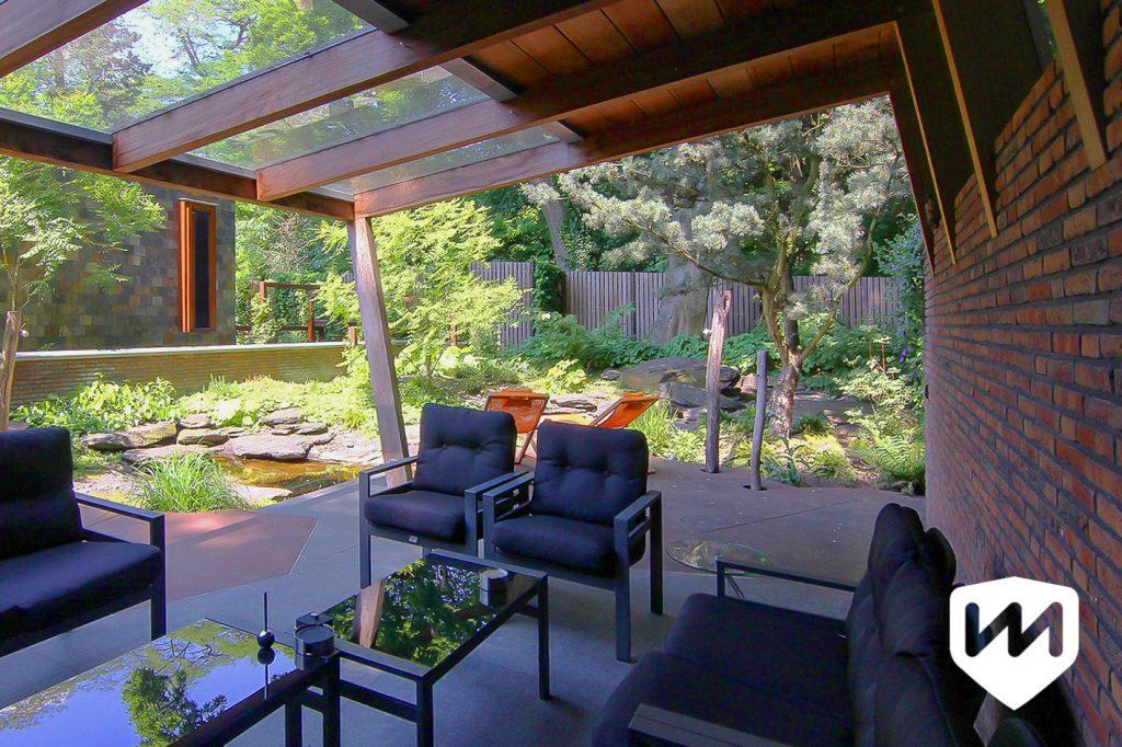 Overkapping tuinarchitect voor natuurlijke bostuin. Zitplek onder overkapping van glas en hout. Tuinarchitect Van Mierlo Tuinen