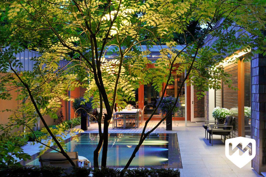 natuur en architectuur in luxe bostuin. luxe infinity overloop zwembad in natuur. Avondverlichting. Tuinarchitect Van Mierlo Tuinen