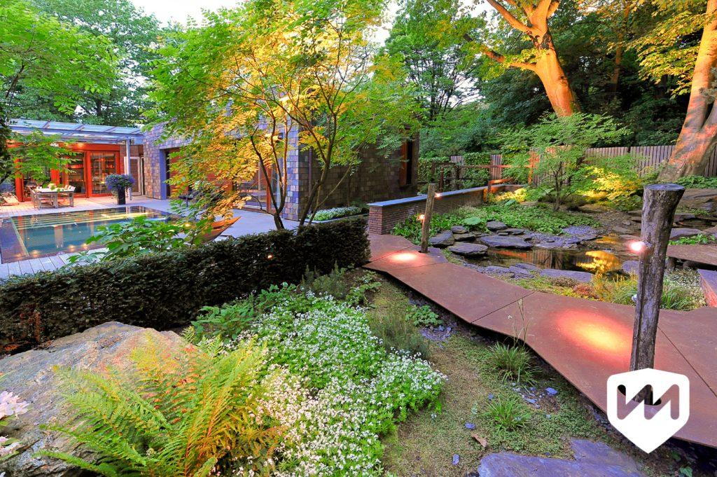 luxe natuurlijke bostuin met avondverlichting. pad van roestige platen. combinatie natuur en architectuur. Tuinarchitect Van Mierlo Tuinen