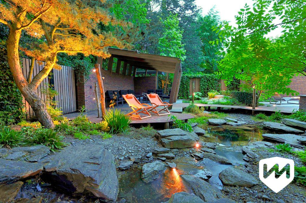 Natuurlijk waterloop met zwerfstenen in luxe bostuin met zitplek in avondverlichting. Tuinarchitect Van Mierlo Tuinen.