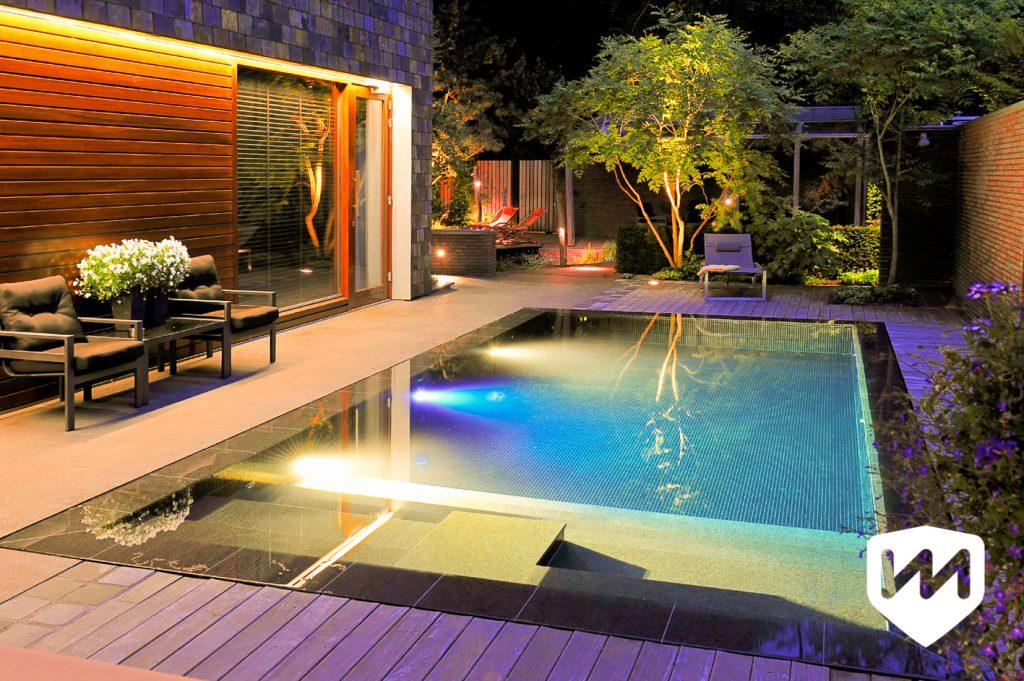 Moderne bostuin met luxe infinity overloop zwembad met avondverlichting. Welnesstuin. Tuinarchitect door Van Mierlo Tuinen.